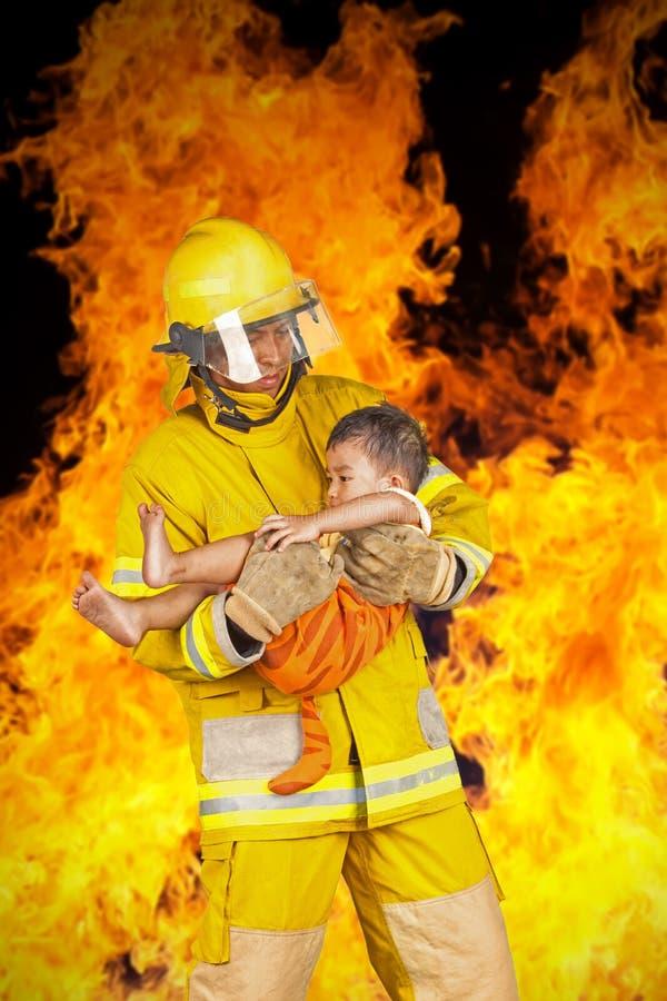 Il vigile del fuoco ha salvato il bambino dal fuoco immagine stock libera da diritti