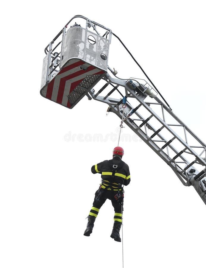 Il vigile del fuoco ha sospeso nel vuoto durante l'esercizio ai pompieri fotografia stock libera da diritti
