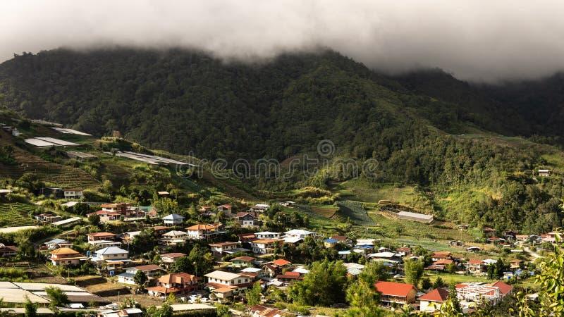 Il villlage sotto la montagna con il cielo nuvoloso immagini stock