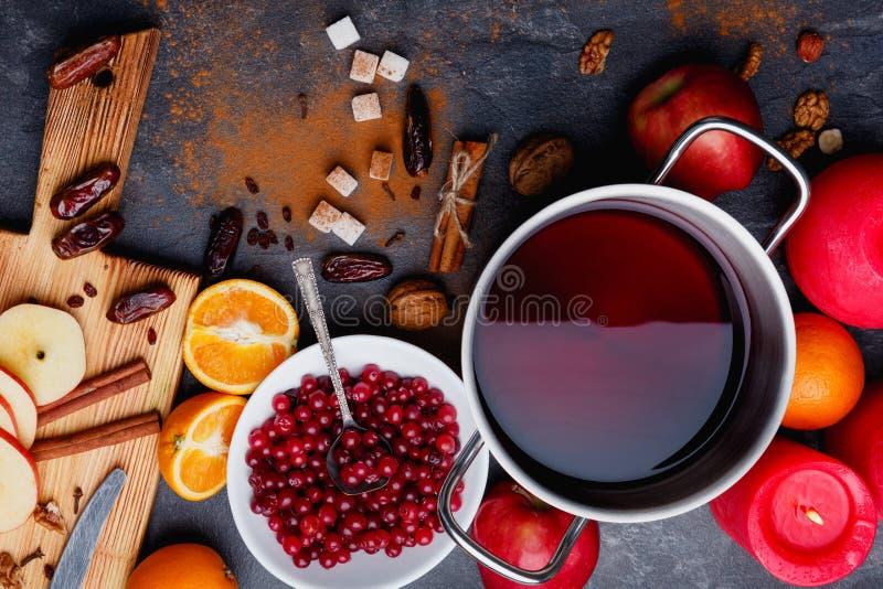 Il vin brulé, piatto con i mirtilli rossi, arance, mele e cannella grattata Vista da sopra immagine stock
