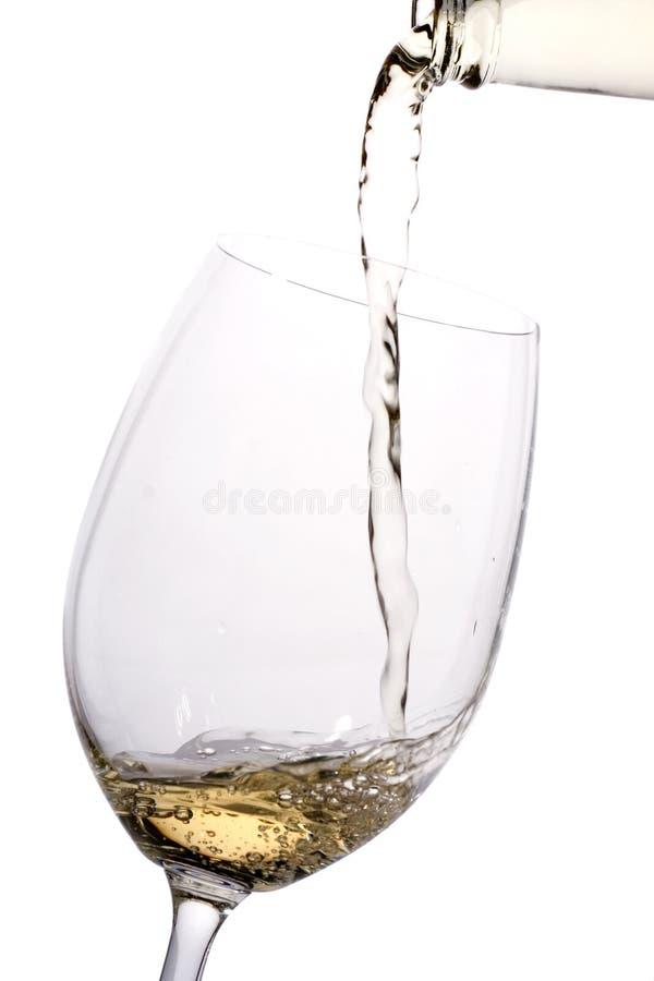Il vino bianco ha versato in un vetro immagini stock libere da diritti