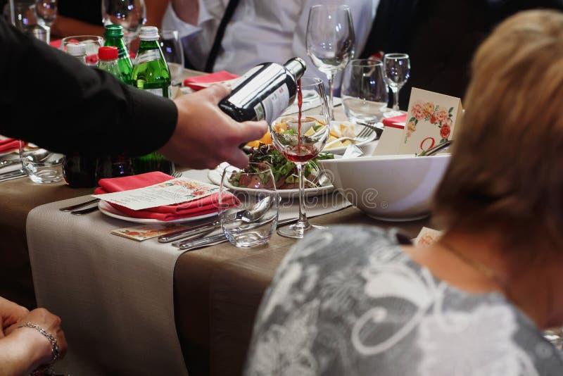 Il vino di versamento del cameriere in vetro dell'ospite ad alla moda di lusso decora immagini stock libere da diritti