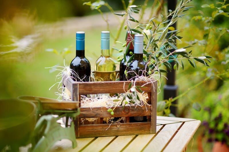 Il vino imbottiglia una cassa di legno decorata con i rami di ulivo fotografia stock