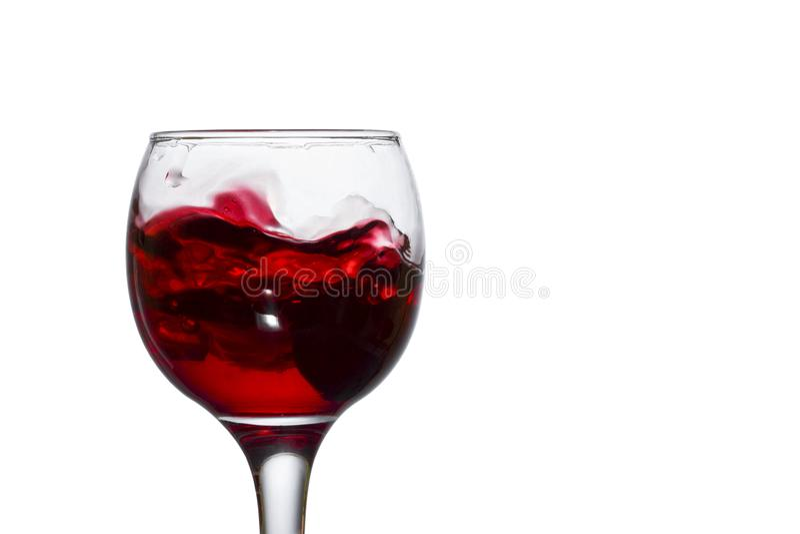 Il vino rosso che spruzza nell'uva caduta scura di vetro cade al fondo fotografia stock libera da diritti