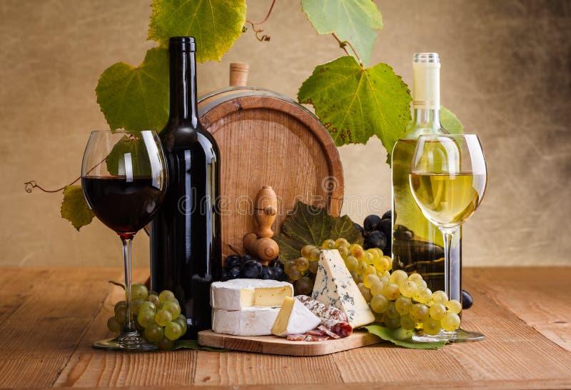 Il vino rosso con formaggio e l'uva blu fanno un spuntino fotografia stock