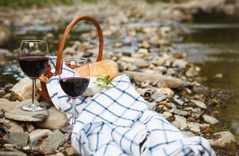 Il vino rosso, il formaggio ed il pane sono servito ad un picnic fotografie stock