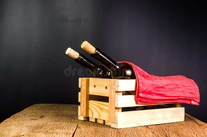 il vino rosso imbottiglia la cassa di legno sul fondo del bordo di legno fotografie stock