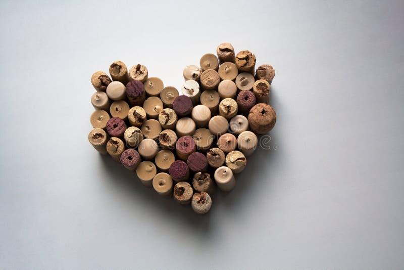 Il vino tappa la composizione a forma di cuore su fondo bianco immagine stock
