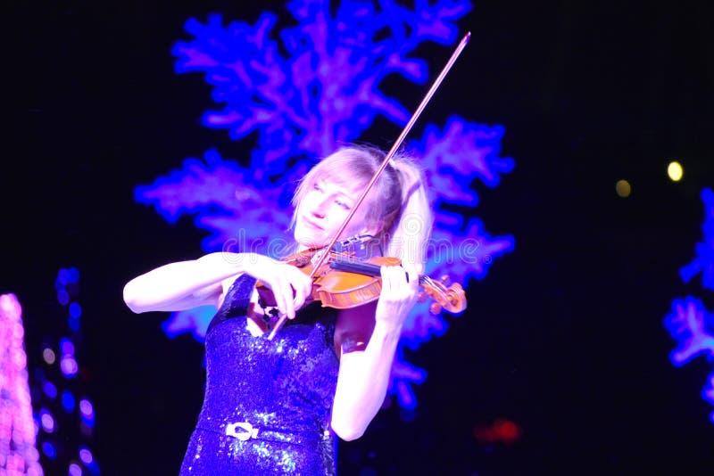 Il violinista della donna che gioca la musica di festa al Natale mostra nell'area internazionale dell'azionamento fotografia stock libera da diritti