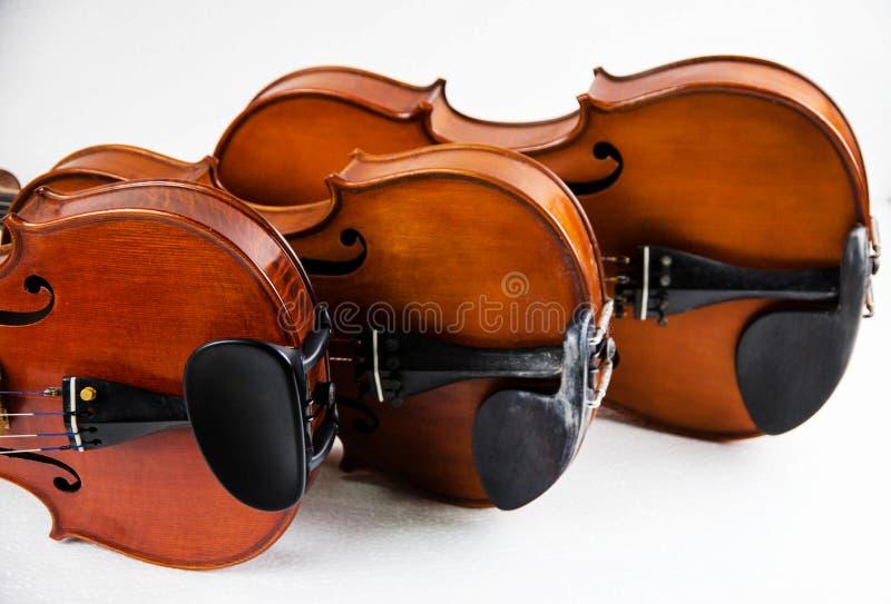 Il violino di legno, tre violini impilati su fondo bianco fotografia stock libera da diritti
