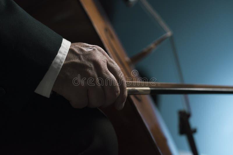 Il violoncellista professionista che esegue le mani si chiude su fotografie stock