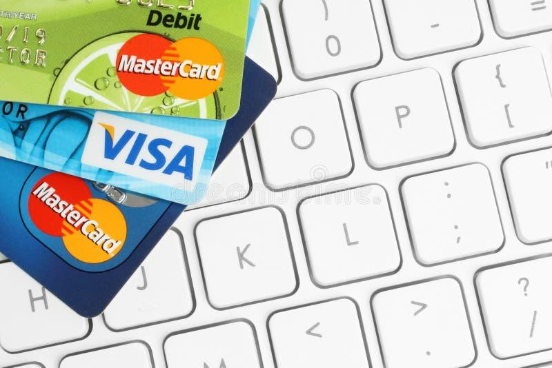 Il visto e Mastercard delle carte sono disposti sul fondo bianco della tastiera fotografia stock