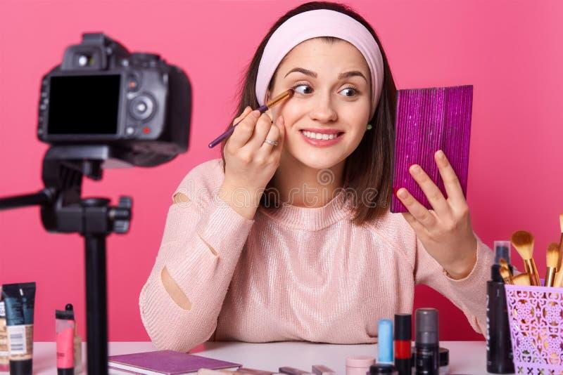Il vlogger sorridente felice si siede davanti alla spazzola delle tenute e della macchina fotografica La giovane signora esamina  fotografia stock libera da diritti