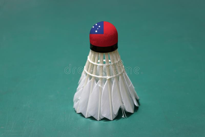 Il volano usato e sulla testa dipinta con la bandiera dei Samoa ha messo verticale sul pavimento verde del campo da badminton immagine stock libera da diritti