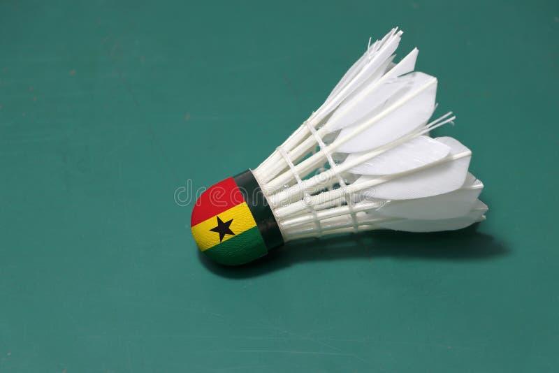 Il volano usato e sulla testa dipinta con la bandiera del Ghana ha messo l'orizzontale sul pavimento verde del campo da badminton immagine stock