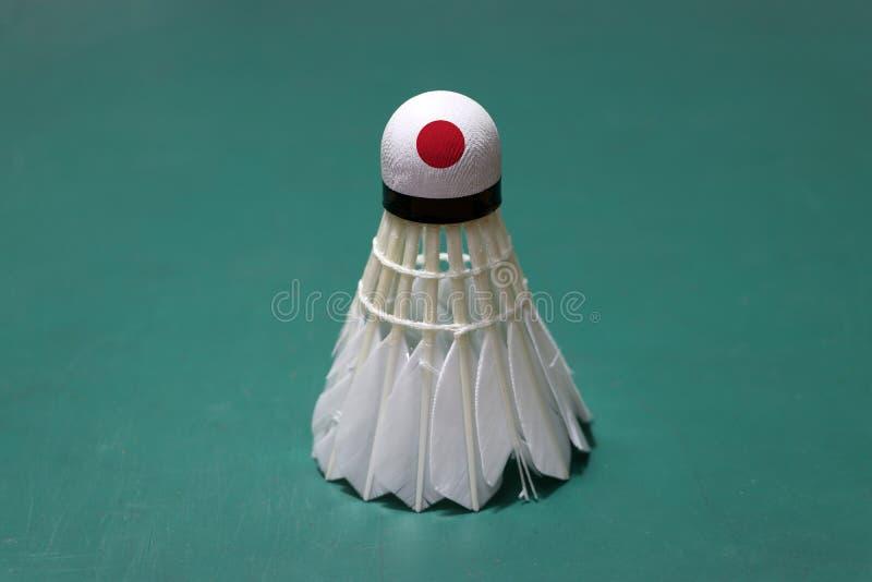 Il volano usato e sulla testa dipinta con la bandiera del Giappone ha messo verticale sul pavimento verde del campo da badminton fotografia stock libera da diritti