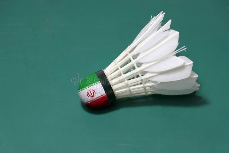 Il volano usato e sulla testa dipinta con la bandiera dell'Iran ha messo l'orizzontale sul pavimento verde del campo da badminton fotografia stock