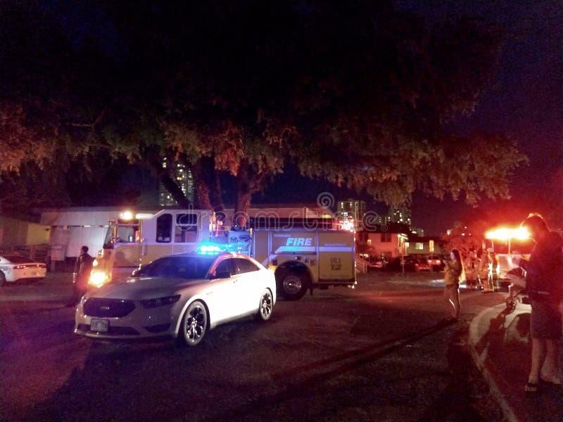 Il volante della polizia del dipartimento di polizia di Honolulu e le luci dei camion dei vigili del fuoco infiammano sulla città immagini stock