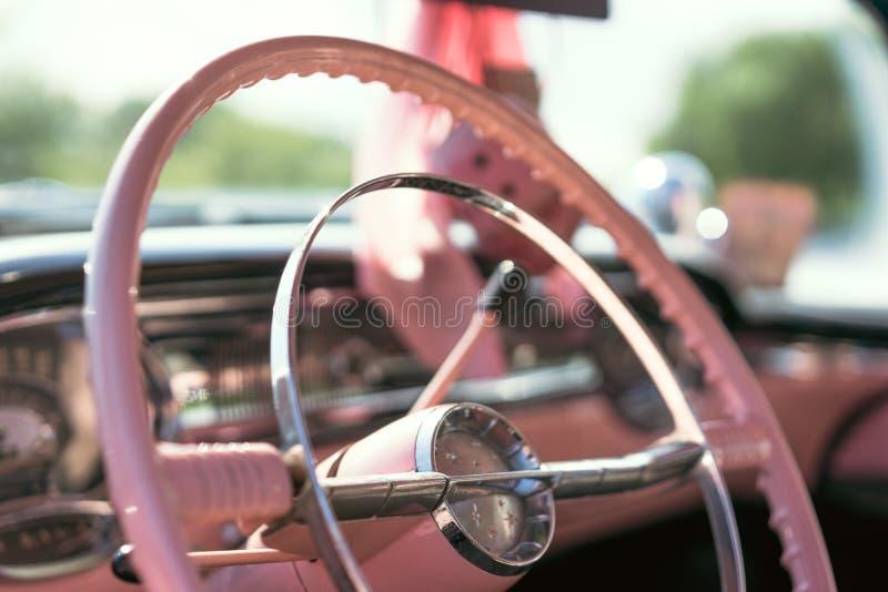 Il volante di un'automobile classica rosa fotografie stock