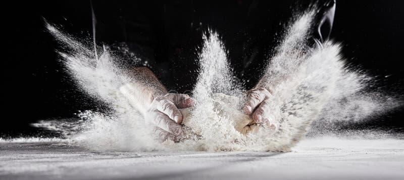 Il volo della farina nell'aria come cuoco unico sbatte la pasta sulla tavola fotografia stock