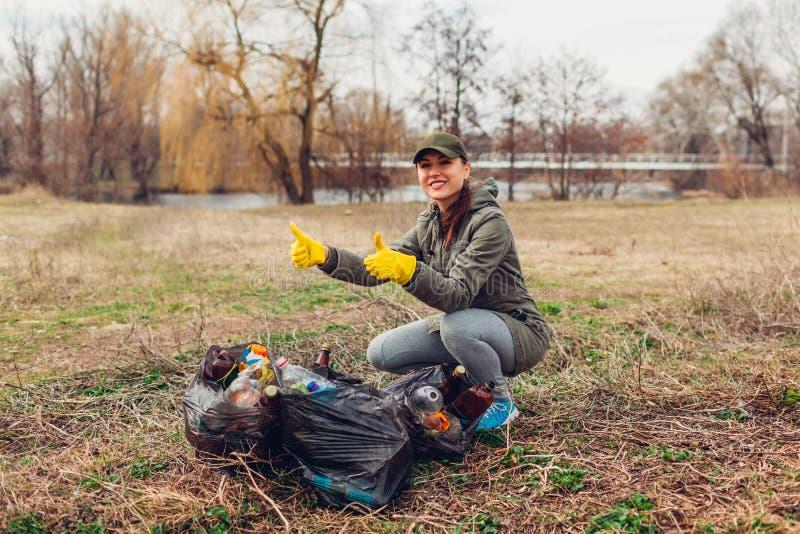 Il volontario della donna ha pulito i rifiuti in parco La gente ha preso l'immondizia e risultato della mostra con le borse piene fotografia stock libera da diritti