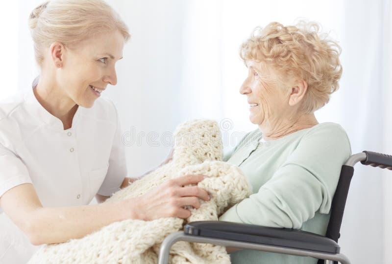 Il volontario sorridente copre la donna più anziana fotografia stock libera da diritti