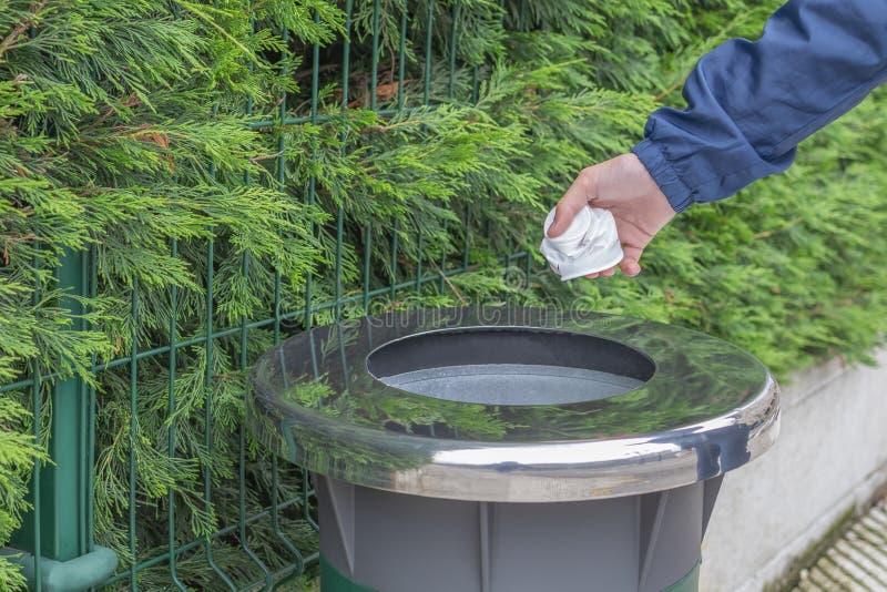 Il volontario teenager nei tiri di una giacca a vento della giacca blu ha raccolto i rifiuti di plastica in un contenitore immagini stock