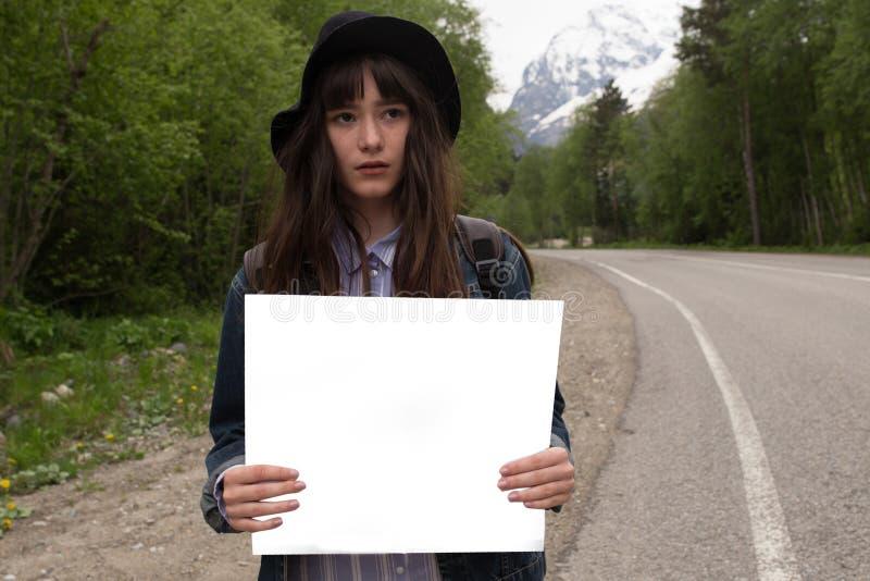 Il vostro testo qui Viaggio e concetto di auto-stop Ritratto della giovane donna graziosa felice che sta con lo spazio in bianco  fotografia stock libera da diritti