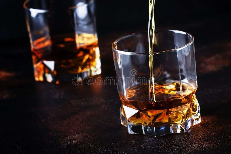 Il whiskey versa dentro il vetro, fondo scuro, fuoco selettivo fotografie stock libere da diritti