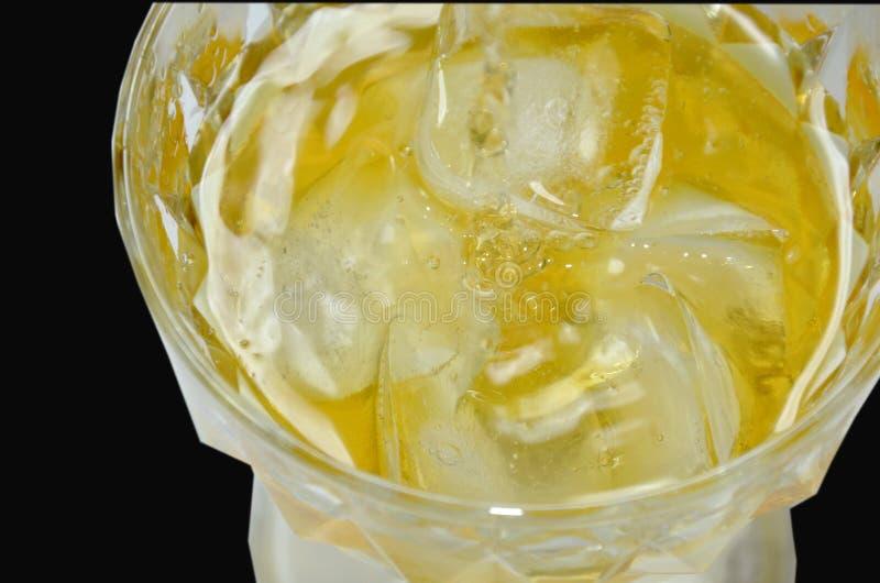 Il whiskey versa su ghiaccio nel fondo nero fotografia stock