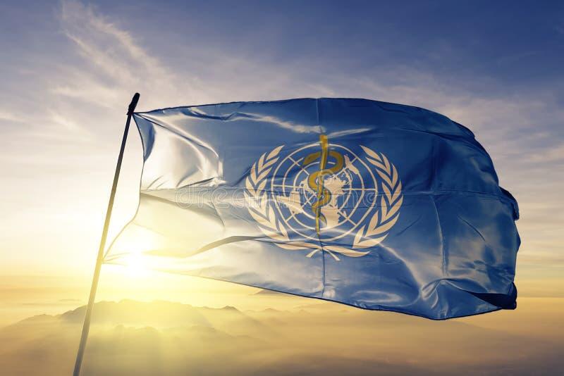 Il WHO dell'organizzazione mondiale della sanità inbandiera il tessuto del panno del tessuto che ondeggia sulla nebbia superiore  fotografia stock
