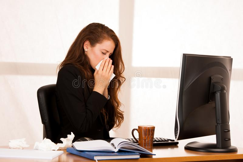 Il woman suffering at work behind the desk in her office stock images