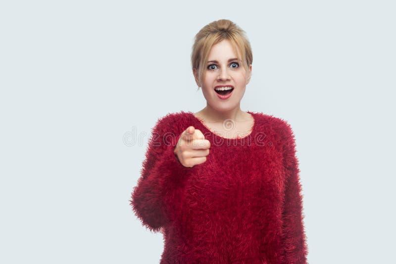 Il wow, è quello era voi? Ritratto di bella giovane donna bionda sorpresa in blusa rossa che sta, esaminante ed indicante la macc fotografie stock libere da diritti