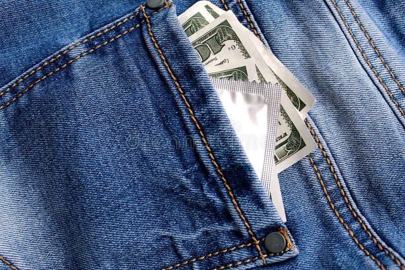Il y a argent et un préservatif dans les jeans empochent image stock