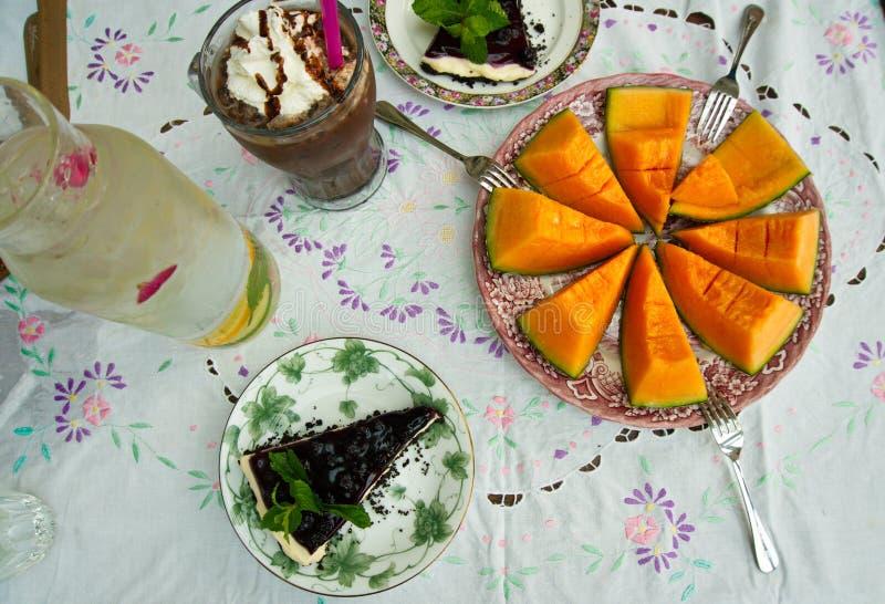 Il y a les tranches de melon de cantaloup, un verre de cacao Iced avec de la cr?me de fouet et deux morceaux de g?teau au fromage image libre de droits
