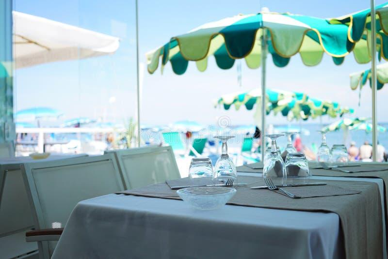 Il y a un restaurant méditerranéen avec des tables sans personnes Les parapluies du soleil dans des tons verts et la plage de mer photographie stock libre de droits