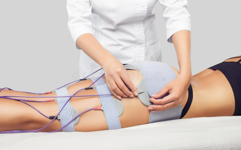 Il y a une femme qui ment et qui fait de la myostimulation anti-cellulite sur les jambes et les fesses dans une beauté photo libre de droits