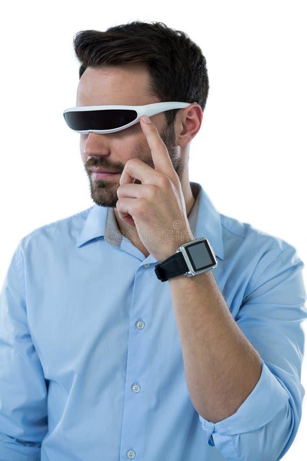 Ilar bärande virtuell verklighetexponeringsglas för man och klockan royaltyfria bilder