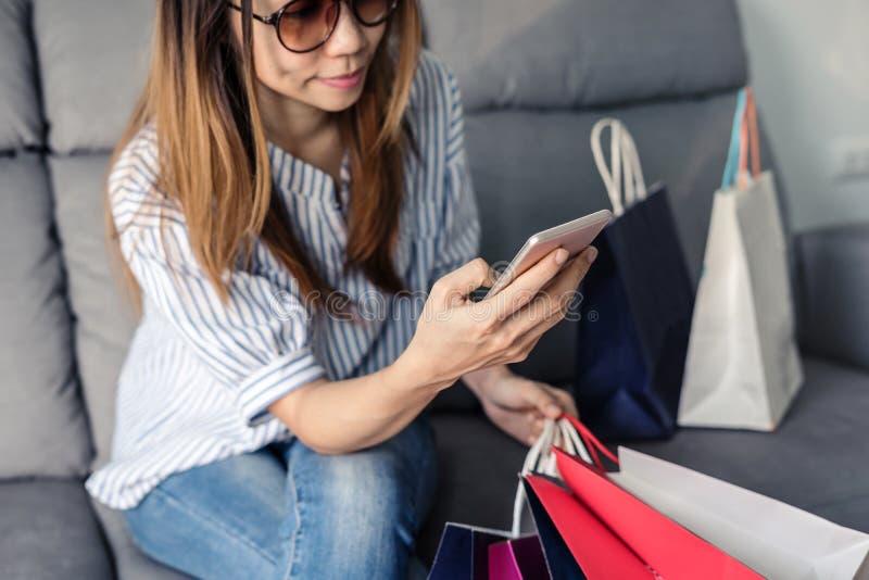 Ilar den hållande kreditkorten för den lyckliga asiatiska kvinnan och telefonen royaltyfria bilder