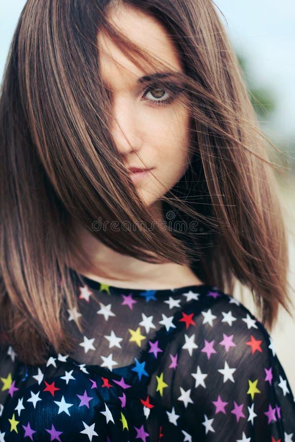 Ilar mörkt hår för den härliga flickan med stora ögon royaltyfria bilder