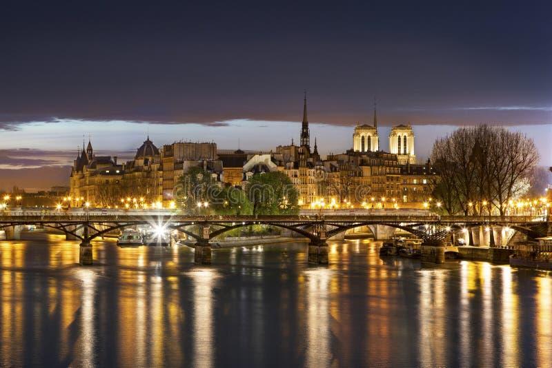 Ile de la cité och Pont des Arts med domkyrkan i Paris vid natt - Frankrike arkivfoto