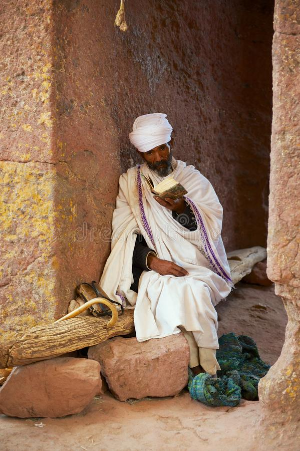 Ilgrim reads bible at the entrance to the unique monolithic rock-hewn church in Lalibela, Ethiopia. UNESCO World Heritage site. stock image