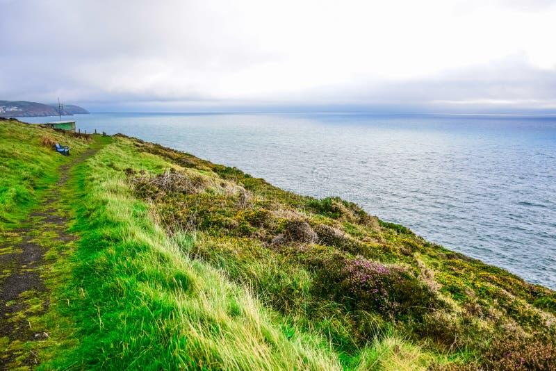 Ilha bonita da paisagem do homem com maneira da caminhada através da grama verde acima no monte imagem de stock