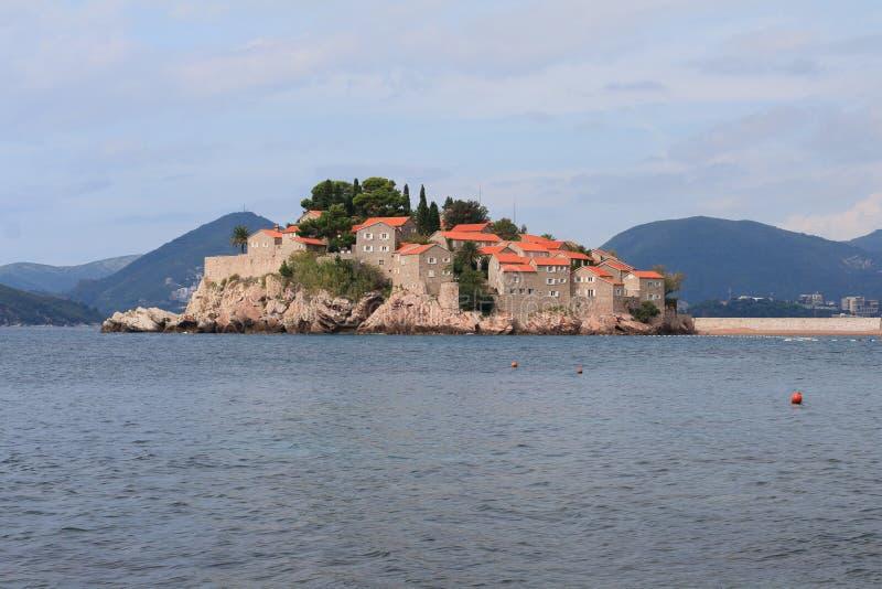 A ilha bonita de montanhas de Sveti Stefan no fundo fotografia de stock royalty free