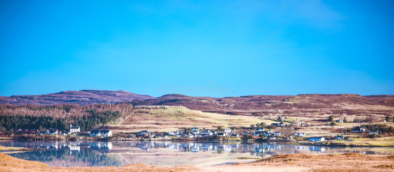 Ilha da paisagem de Skye - o Loch Dunvegan, vila de Dunvegan, urze cobriu montes imagem de stock