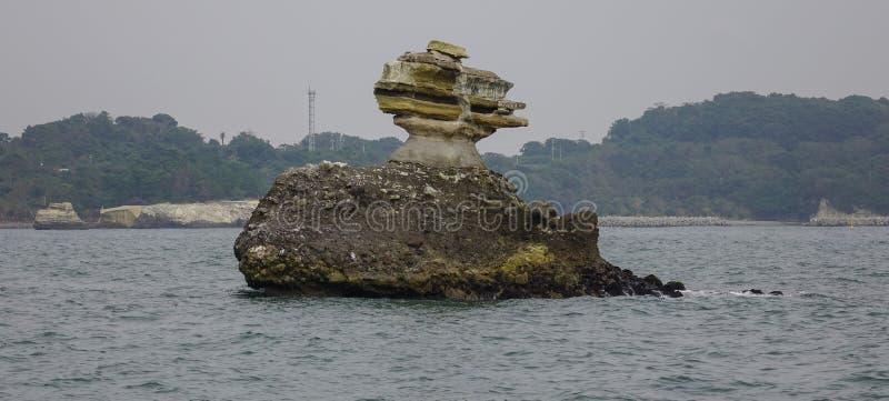 Ilha da rocha no mar no dia chuvoso imagens de stock