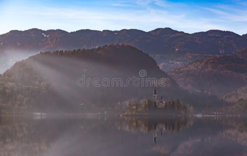 Ilha da vista com a igreja Católica no lago sangrado Bled é uma das atrações turísticas as mais surpreendentes em Eslovênia Lan d imagem de stock royalty free