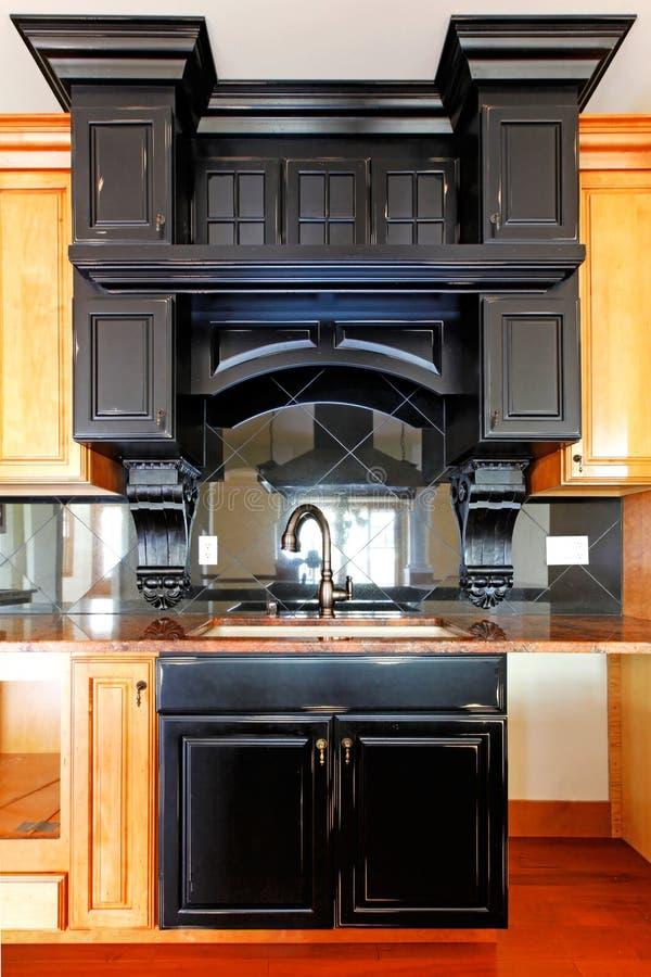 Ilha de cozinha e gabinetes de madeira feitos sob encomenda do fogão. Interior home luxuoso novo. foto de stock