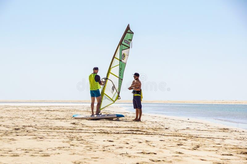 Ilha de Fuerteventura, Espanha 12 de junho de 2017: o homem ativo novo toma uma lição do windsurfe com um instrutor no oceano foto de stock