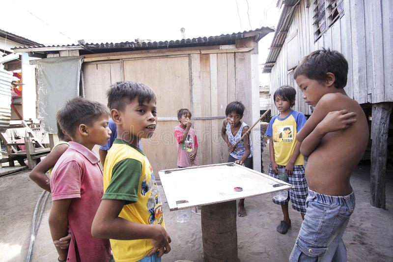 ILHA DE MABUL, SABAH, MALÁSIA - 2 DE MARÇO: a criança aciganada do mar local está jogando carom um 3 de março de 2013 na ilha de  foto de stock